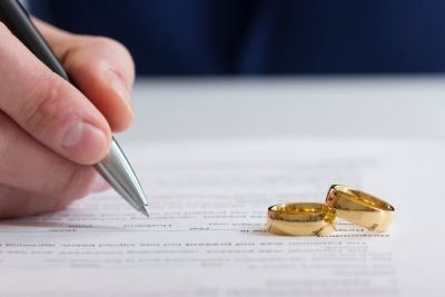 a person signs divorce papers with two gold wedding rings sitting on top